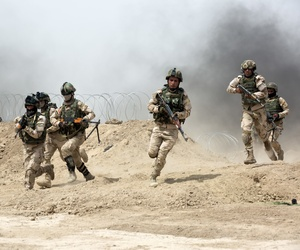 Iraqi soldiers run through a breach in a berm while training at Camp Taji, Iraq, on June 2, 2015.