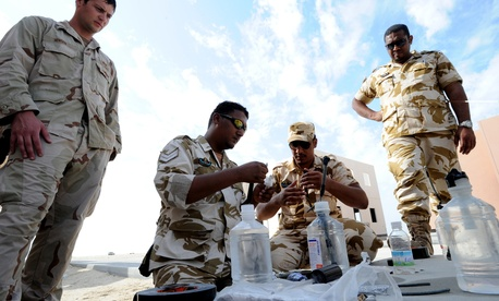 An EOD technician observes Royal Bahrain Navy diverse and Royal Bahrain Army EOD as they assemble blasting devices during Neon Response 2012.
