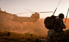 An NCO directss a UH--47 Chinook helicopter onto a haste landing zone, in Charbaran Valley, Afghanistan.