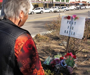 Laura Spaeth looks at a memorial honoring American hostage Kayla Mueller on the corner of courthouse plaza in Prescott, Ariz., Tuesday, Feb. 10, 2015.