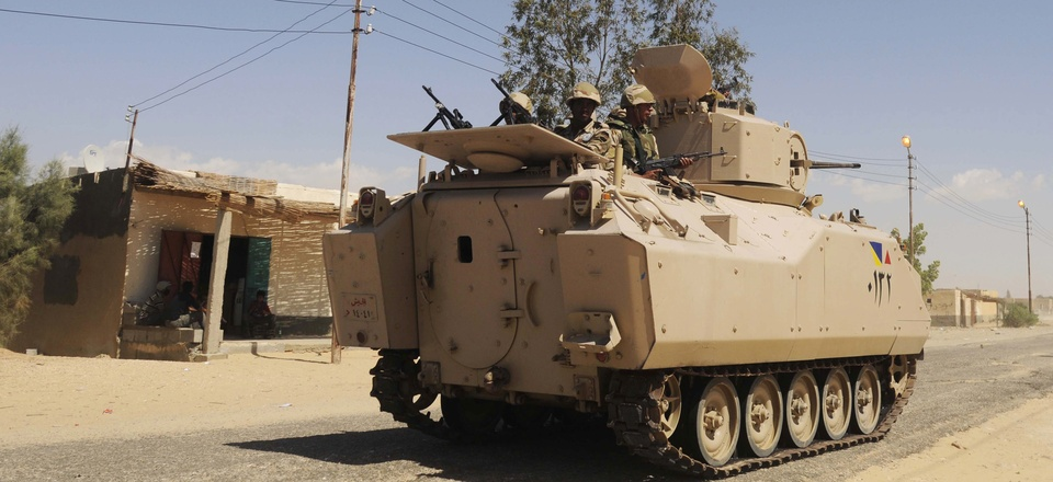 Egyptian Army soldiers patrol in an armored vehicle backed by a helicopter gunship during a sweep through villages in Sheikh Zuweyid, north Sinai, Egypt, on May 12, 2013.