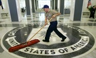 A workman quickly slides a dustmop over the floor at the Central Intelligence Agency headquarters during a visit by President George W. Bush, on March 3, 2005.