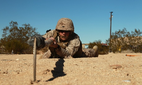 An enlisted Marine employs a bamboo sickle stick to search for buried improvised explosive devices at the Combat Center's Range 800 Feb. 13, 2013.