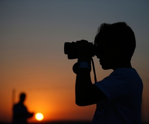 A youth uses binoculars to look at Turkish army tanks holding positions, near the border with Syria, in the outskirts of the village of Elbeyi, east of the town of Kilis, in southeastern Turkey, Thursday, July 23, 2015.