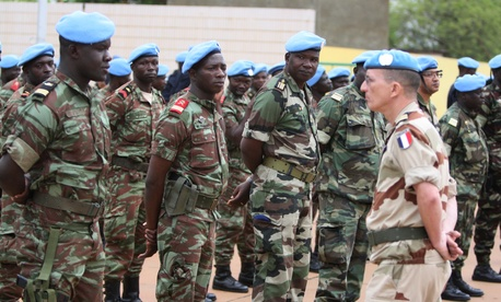 A French soldier stands alongside African troops who helped France take back Mali's north earlier this year, as they participate in a ceremony formally transforming the force into a United Nations peacekeeping mission, in Bamako, Mali, July 1, 2013.