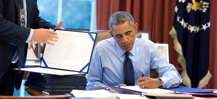 President Barack Obama signs bills in the Oval Office in 2014.