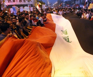 Protesters chant in support of Iraqi Prime Minister Haider al-Abadi as they carry a large national flag during a demonstration in Tahrir Square in Baghdad, Iraq, Friday, Aug. 14, 2015.