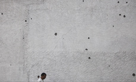 An Indian border villager walks past a house wall with mortar shell damage in Ranbir Singh Pura, 23 miles from Jammu, India.