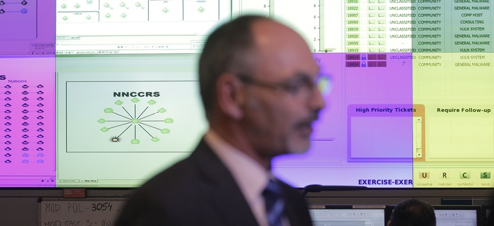 Director Ian West walks in front of computer screens at the NATO Computer Incident Response Capability technical center, at NATO's military headquarters.