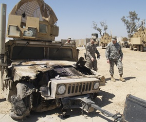 A humvee damaged by an EFP is looked over at the U.S. Army Patrol Base of the 2-28 Infantry in Al Hillah, 62 miles south of Baghdad.