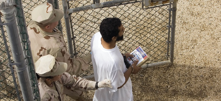 In this file photo, reviewed by the U.S. Military, guards escort a detainee carrying a book from the library trailer to the detention facility in an open air common area at Camp Delta 4 in Guantanamo Bay.