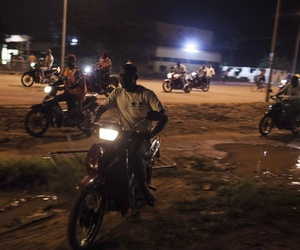 People on motor bikes used as taxi drive around following demonstrations near the presidential palace after soldiers arrested Burkina Faso's transitional president and prime minister in Ouagadougou, Burkina Faso, Wednesday, Sept. 16, 2015.