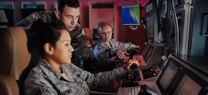 USAF Master Sgt. Jennifer Oberg explains the features of a ground control station to Staff Sgt. Jason Avera and Senior Airman Raquel Martinez.