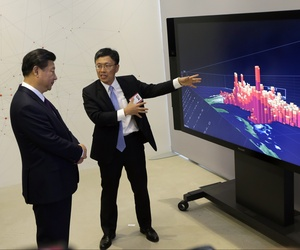 Chinese President Xi Jinping listens as Microsoft's Harry Shum demonstrate how Microsoft Surface technology can be used for data visualization.