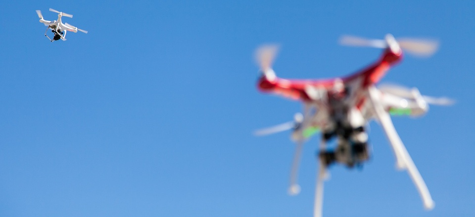 Two quadcopters in a clear sky.