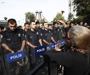 A protester throws carnations to Turkish police blocking the way to the site of Saturday's explosions in Ankara, Turkey, Sunday, Oct. 11, 2015. Scuffles broke out as police prevented pro-Kurdish politicians and other mourners from laying carnations at the