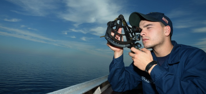 Quartermaster Seaman Pasquale V. Verrastro uses a sextant to find the range of a foreign vessel on the bridge wing of the guided-missile destroyer USS Ramage (DDG 61) in 2014.