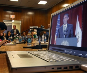 aiza Ali, Council on American-Islamic Relations (CAIR) community affairs director, watches U.S. President Barack Obama's speech from Cairo projected on a big screen off a laptop computer with New York area Muslim leaders at the InterChurch Center in New Y