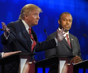 Ben Carson, right, watches as Donald Trump speaks during the CNBC Republican presidential debate at the University of Colorado, Wednesday, Oct. 28, 2015, in Boulder, Colo.