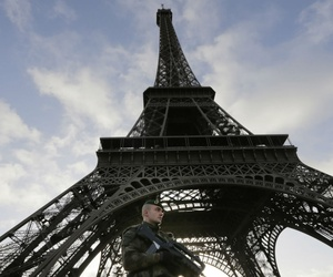 A French soldier stands guard at the Eiffel Tower, which was closed Sunday.