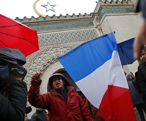 """A French Muslim, of Algeria origin, who wants to be named """"Cherif"""" talks to the media, holding a French flag, in front of the Great Mosque of Paris after the Friday priest, in Paris, France, Friday, Nov. 20, 2015 one week after the Paris attacks."""
