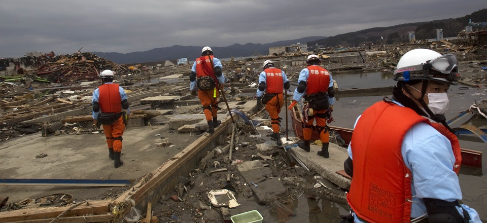 Japanese recovery officials search through the ruins of the leveled city of Minamisanriku, in northeastern Japan, Tuesday March 15, 2011.