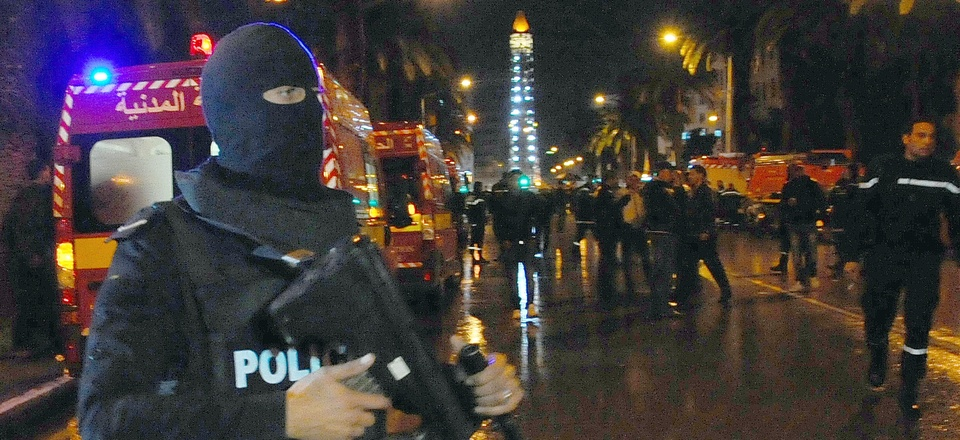 A hooded police officer prevents media from aproaching the scene of a bus explosion in the center of the capital, Tunis, Tunisia, Tuesday, Nov. 24, 2015.