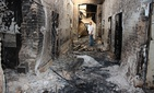 In this Oct. 16, 2015, file photo, an employee of Doctors Without Borders stands inside the charred remains of their hospital after it was hit by a U.S. airstrike in Kunduz, Afghanistan.