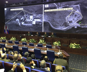 Russian top military officials speak to the media in front of an aerial images they say are oil trucks near Turkey's border with Syria displayed by the Russian Defense Ministry at a briefing in Moscow, Russia, Wednesday, Dec. 2, 2015.
