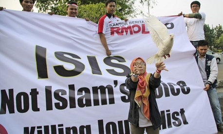 A Muslim woman releases a dove as a symbol of peace during a rally against the Islamic State group, in Jakarta, Indonesia, Friday, Sept. 5, 2014.