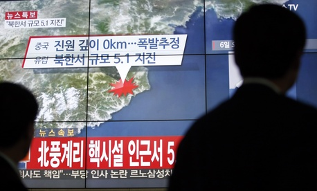People walk by a screen showing the news reporting about an earthquake near North Korea's nuclear facility, in Seoul, South Korea, Wednesday, Jan. 6, 2016.