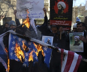 In this Sunday, Jan. 3, 2016 file photo, Iranian demonstrators burn representations of the U.S. and Israeli flags during a demonstration in front of the Saudi Arabian Embassy in Tehran, Iran.