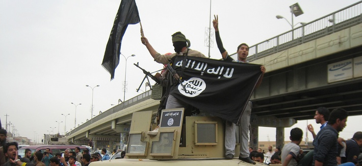In this Sunday, March 30, 2014, file photo, Islamic State group militants hold up their flag as they patrol in a commandeered Iraqi military vehicle in Fallujah.