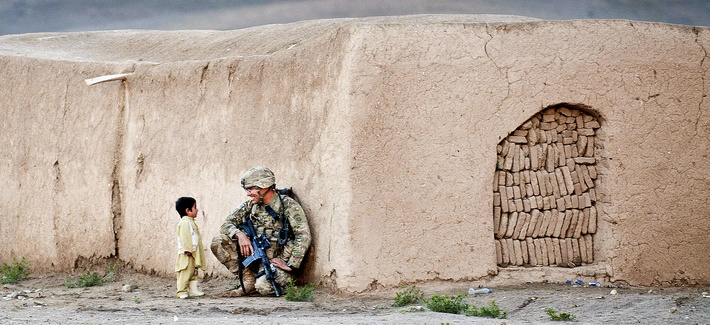 Sgt. Joshua Smith, a paratrooper with the 82nd Airborne Division's 1st Brigade Combat Team, chats with an Afghan boy during an Afghan-led clearing operation April 28, 2012, Ghazni province, Afghanistan.