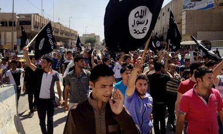 In this June 16, 2014 file photo, demonstrators chant pro-Islamic State group, slogans as they carry the group's flags in front of the provincial government headquarters in Mosul.