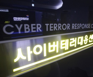 In this July 16, 2013 file photo, a woman walks by a sign at Cyber Terror Response Center of National Police Agency in Seoul, South Korea.