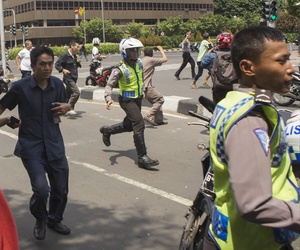 People, including unarmed police officers, flee from the scene after a gun battle broke out following an explosion in Jakarta, Indonesia Thursday, Jan. 14, 2016.