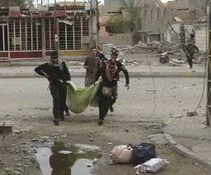 Iraqi security forces and allied Sunni tribal fighters evacuate a badly injured woman after she was shot by Islamic State group fighters as she was trying to cross from neighborhoods in Ramadi, Iraq, Monday, Jan. 4, 2016.