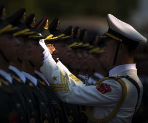 An officer adjusts the hat of a Chinese People's Liberation Army (PLA) honor guard member as they practice lining up before a welcoming ceremony for Singaporean President Tony Tan Keng Yam at the Great Hall of the People in Beijing, Friday, July 3, 2015.