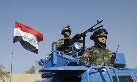 In this Nov. 22, 2011 file photo, the Iraqi flag waves while federal police parade in Baghdad.