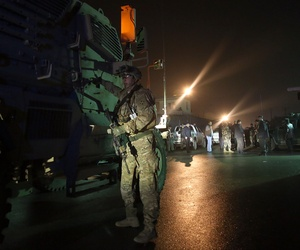 A U.S. soldier stands near his vehicle at the site of a suicide attack near a compound belonging to foreigners in Kabul, Afghanistan, Monday, Jan. 4, 2016.