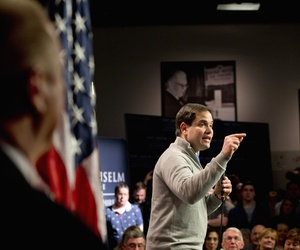 Security stands at left as Republican presidential candidate, Sen. Marco Rubio, R-Fla. speaks during a town hall meeting at the Saint Anselm Institute of Politics in Manchester, N.H., Thursday Feb. 4, 2016.