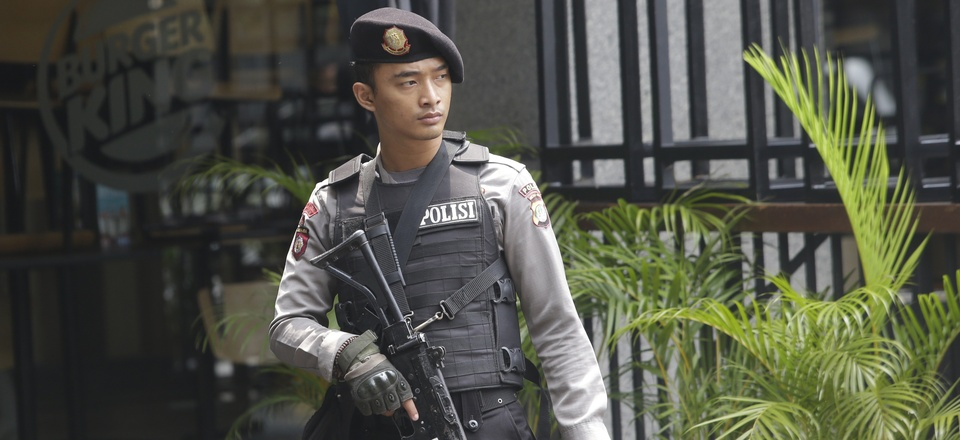 An armed policeman stands in front of a Burger King restaurant near the Starbucks cafe where Thursday's attack occurred in Jakarta, Indonesia, on Friday, Jan. 15, 2016.