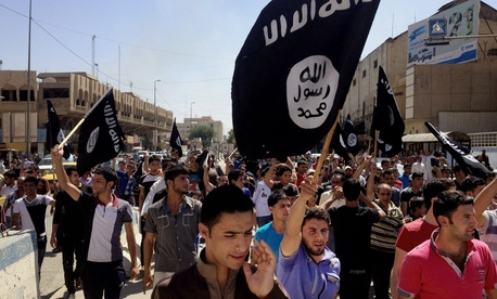 In this Monday, June 16, 2014 file photo, demonstrators chant pro-Islamic State group slogans as they wave the group's flags in front of the provincial government headquarters in Mosul, Iraq.