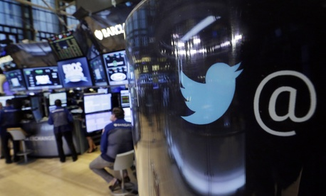 The Twitter logo appears on a phone post on the floor of the New York Stock Exchange, Oct. 13, 2015.