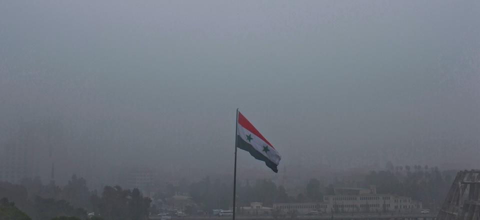 A Syrian national flag waves as heavy fog envelops the capital city of Damascus, Syria, Wednesday, Feb. 24, 2016.