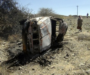 People gather near a destroyed car that was carrying militants in the Sawmaa area of al-Bayda province, Yemen, Saturday, April 19, 2014.