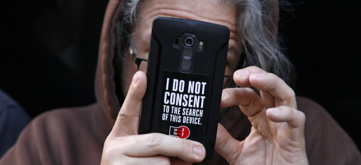 A man holds up his phone during a rally in support of data privacy outside the Apple store Tuesday, Feb. 23, 2016, in San Francisco.