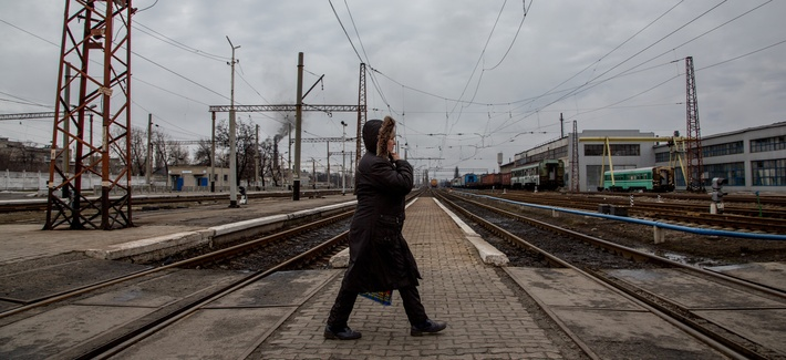 In this photo taken on Friday, Feb. 5, 2016, a local woman walks along a rail-road crossing in Debaltseve, eastern Ukraine. Money from Russia helps to rebuild the eastern Ukrainian town of Debaltseve, a strategic rail hub that rebels pounded  recently.
