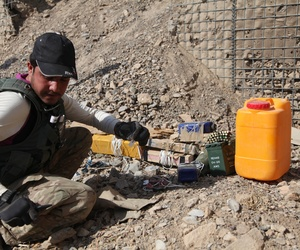 An Afghan Civilian Mine Removal Group (CMRG) member investigates IEDs during a training simulation in Panjwai district, Kandahar province, Afghanistan, Nov. 19, 2013.